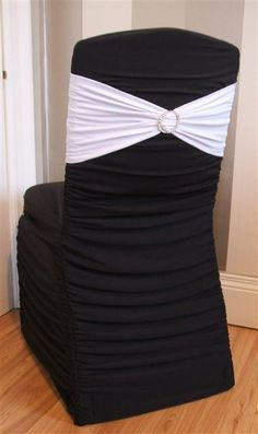 Black ruffled chair cover with white band & bling!! But out chairs will be a tight spandex vs ruffled