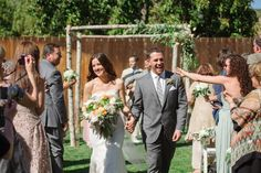 Recessional -- we would be happy too at this sunny outdoor wedding ceremony. Modern Jewish Wedding in San Luis Obispo, CA. From Modern Jewish Wedding Blog. Photo by Marcella Treybig Photography. #chuppah #graysuit #bride #groom #bouquet #jewishwedding #inspiration
