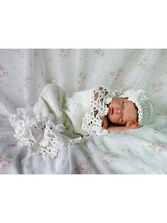 This beautiful design is worked in both knitting and crochet! The cocoon body and hat are knitted in simple stockinette stitch using a worsted-weight yarn. Instructions are included for both knitting in the round and flat. The lace and flower are crocheted using a size 5 crochet cotton thread or a fingering-weight yarn. Size: Newborn to 3 months.