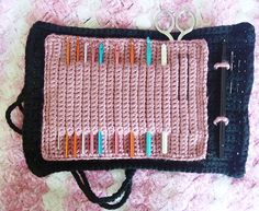 I am a pack rat for crochet hooks -- and I try to carry them all with me whenever I go somewhere (since I never know what I will be in the mood to work on). I got tired of all of my hooks and notions just rumbling around in my bag and came up with this simple little pattern for a hook roll that holds all of my hooks, a couple of needles, a pen, and even a pair of small scissors!