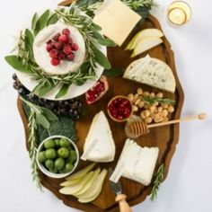 A winter-themed cheese board, filled with decadent cheeses alongside sweet and…