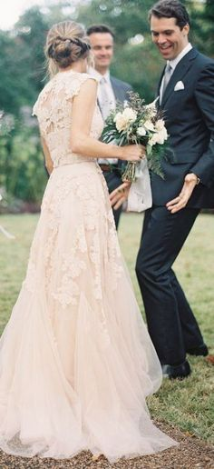 Blush wedding dress with beautiful lace overlay back and cap sleeves plus frothy skirt.