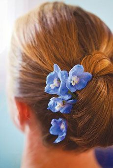 Chignon, styled by Donnell Robinson of Gustavo Cosmetics & Skincare, adorned with bright blue delphiniums.  Photo by Holland Photo Arts #weddings
