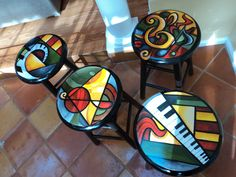 Hand painted stools in bright abstract patterns.