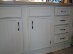 Cabinet update. To spruce up ugly cabinets for CHEAP, attach bead board and trim. You can get cheap hardware on Amazon.com. I did 13 cabinets and 8 drawers for $150 including paint.