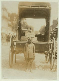 African American Boy, approximately 7 years old, working carrying 25 lb. bags of flour from wagon to stores,  making 25 cents a week. Wilmington, Delaware1910