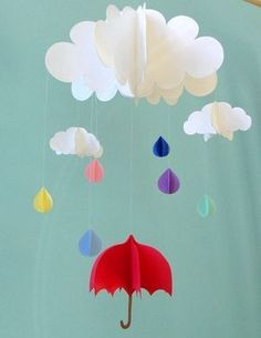 Rainbow-colored raindrops fall from the clouds above a little red umbrella in this adorable 3D mobile. Made of card stock paper, the clouds, raindrops, and umbrella are light enough to be moved by even a gentle breeze. Mobile consists of three 3 dimensional clouds ranging from 2.5 inches to 8 inches in width, 6 raindrops, and 1 umbrella measuring 3.5 x 4 inches. Total length of mobile is approximately 14 inches. *This item is made to order, and raindrops and umbrella can be made with…