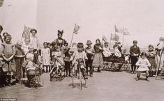 Children holding American flags while riding tricycles and wagons on the rooftop garden of Ellis Island were the offspring of detained or waiting immigrants
