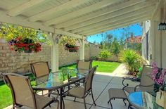 The backyard features a covered patio with a tiled overhang and small lawn area which requires little maintenance.
