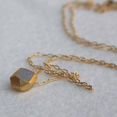 Concrete couldn't possibly be a girl's best friend. But what if it were carved into a diamond shape, wrapped in gold plating, and dangled from a gold fill chain?