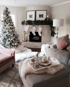 Christmas tree, white brick fireplace, velvet grey couch, velvet pink loveseat, upholstered square ottoman. White neutrals