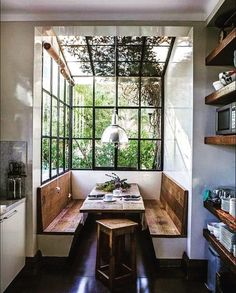 Charming built-in banquettes made of natural organic, modern rustic booths in breakfast area of kitchen with black industrial windows and ceiling. #rusticdecor #modernfarmhouse #banquette
