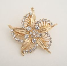 """• Main Color(s): gold • Materials: rhinestones, goldtone metal • Maker: unknown • Approximate Year: c1990s • Size: 1-7/8"""" diameter This pin has a stylistic floral design accented with sparkling chaton"""