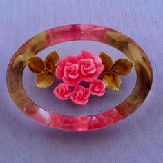 This is a clear Lucite oval brooch, reverse beveled, and reverse-carved and painted, to give the illusion of an embedded delicate pink rose bouquet,