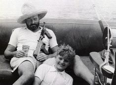 This is renowned author Ernest Hemingway relaxing on his boat with a pina colada, a tommy gun, and his son Jack circa