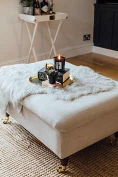 Grey Padded Footstool Ottoman Coffee Table With Gold Accents And Jo Malone Oud And Velvet Rose Candle