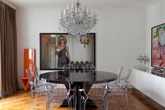 A sala de jantar exibe extrema elegância com mesa de laca preta brilhante, da MiCasa, servida por cadeiras Louis Ghost desenhadas por Philippe Starck e compradas na A Lot Of. O lustre e os castiçais de cristal, do antiquário Ana Luiza Wawelberg, conferem um toque de época ao espaço que também possui tela de Cristina Canale (à dir.), da Galeria Nara Roesler, e aparador-bufê da Casual. Na outra parede, a foto da modelo Eva Herzigova e a cadeira laranja, desenhada pelo arquiteto Aurélio Flores…