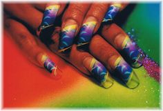 Long curved nails dressed up with purple, yellow and blue art - by : Pilar