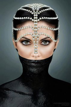 Swarovski crystal headdress. Or diamonds? Black body paint halfway up the face. Smokey eye. Portrait. Headshot