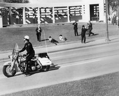 About 30 seconds after the assassination, photographers on the grassy knoll race to the scene as Bill and Gayle Newman shield their children, Billy and Clayton, on the ground. The Newmans were the closest civilian eyewitnesses to the assassination.