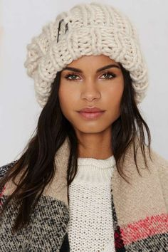 The Milla Beanie is made in a chunky ivory knit and features an oversized shape, cuffed edge, and silver pin at the side.