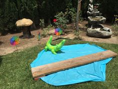 """My daughters Dora the Explorer birthday party... Kids had to """"cross crocodile bridge"""" to get to the jolly jumper. The alligator is from a ring toss game, water is a round table cover."""