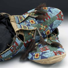 """Moccasins Lakota or Nakoda (Assiniboine). Beaded hide, tin, buffalo fur. Length 26 x width 12 x height 8 cm. c. 1880. Said to belonged to Big Bear, Cree Chief. According to the donor W.B. Bemister the moccasins were """"worn by Big Bear, at the time he was captured in 1885."""" Altough Big Bear was Cree, the donor states that the moccasins are Sioux. ROM. Ф. Ф. Ф."""