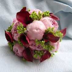 Hand tied bouquet of pink peonies, red calla lilies, green hypericum berries, green sinensis.