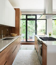 I like the wood cabinets and light countertops. Good natural light in this room. Nice clean lines.