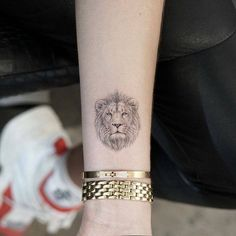 Single needle lion portrait tattoo on the wrist.