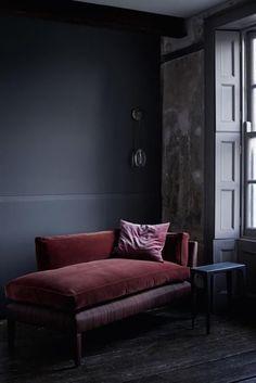 Rich dark velvet lounger ; dark walls ; celestial pebble wall light ; moody room
