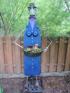 "A garden lady I made from a ironing board and lots of other stuff. Inspired by Jim Shores the ""junk artist"""