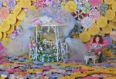 Fairy House  A delightful Gazebo covered with netting, ribbons and flowers.  What little fairy wouldnt want to live here! A pretty matching chair and a little fairy comes with this pretty cottage. There is a small table with her food and dishes.  A gazing globe, suncatcher and other surprises abound in this house. (A bottle of fairy dust, a globe of dried roses, a pink owl, sea horses, keys, vines, and other baubles and beads!)  What a fun place for her friends to visit!  Youll love visiting…