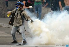 An opposition activist clashes with police during a protest in Caracas, Venezuela