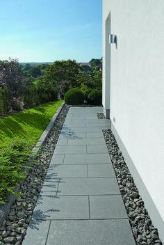 Hier entlang ins Gartenparadies, zur Terrasse! Der angelegte Plattenweg mit Kiesbegrenzung führt ums Gebäude. #rinnbeton #design #gartengestaltung