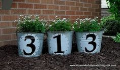 Cute idea for the front flower bed!! House numbers on some old buckets!