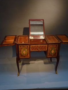 Rectangular top with canted corners with a marquetry of a bust on a vase-shaped stand flaked by various urns and jugs below a lambrequin and drapery. The hinged central panel top enclosing an easled toilet mirror and flanked to each side by a hinged compartment with green fabric lining. The front with five drawers and a sliding green fabric lined writing panel. The front and sides with a marquetry of an urn in an oval ribbon-tied medallion. On four cabriole legs with ormolu sabots.