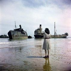 A woman on Omaha Beach looks out at ruined ships used in the D-Day storming of Normandy, France. Photograph by David Seymour, June 1944 allied forces stormed these very beaches, beginning the liberation of Western Europe from Nazi control during WWII. D Day Normandy, Normandy France, Normandy Ww2, Normandy Beach, Omaha Beach, D Day Invasion, 2017 Image, Unseen Images, Historia Universal