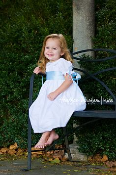Girls in white dresses with blue satin sashes