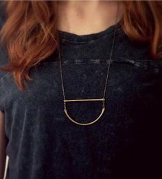 Bar & Arch Hammered Brass Necklace, this geometric necklace is all about turning a negative into a positive.