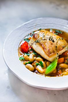 A soulful warming bowl of Cannellini Bean Stew topped with pan-seared Sea Bass. For nightshade free, substitute mango chunks for tomatoes. Fish Recipes, Seafood Recipes, Dinner Recipes, Chilli Recipes, Italian Recipes, Dinner Ideas, Paella, Easy Delicious Recipes, Pisces