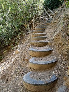 Recycled tires outdoor stairs on steep hillside.  Imagine them painted a bright color, with lots of plants around.  Looks like these might need a railing too!