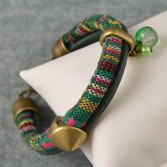 Pulsera estampado de cordón étnico en tonos verdes y piezas de zamak y cristal