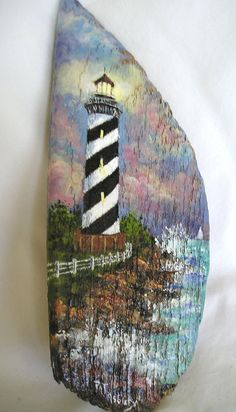 An original painting of a striped lighthouse. Painted with acrylics on driftwood and sealed on all sides. This piece measures 10 inches tall and 3 3/4