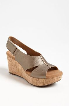 "Clarks® England 'Cassylynn Lizzie' Sandal. A cushioned footbed and cutout vamp designed to facilitate air flow lend comfy contours to an earthy sandal set on a cork-wrapped wedge.   * Approx. heel height: 3"".   * Adjustable slingback strap with hook-and-loop closure.   * OrthoLite® footbed.   * Nubuck leather or leather upper/suede and synthetic lining/rubber sole.   * By Clarks® England; imported.   * Women's Shoes."
