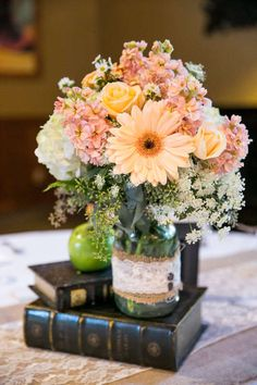 Great idea for a wedding centerpiece--lush floral in pastel colors stacked on vintage books                                                                                                                                                                                 More