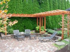Like the tall hedges with L shape pergola and patio seating with flower beds Small Backyard Landscape Design Ideas