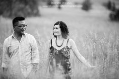 A couple walking together through a field during their engagement shoot