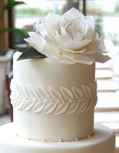 Gateaux Inc Single Tier fondant with white leaves around a middle border and a sugar paste flower top.