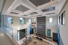 Contemporary living room shot from the second floor loft overlooks a glass railing, slate fireplace surround, custom furniture, high gloss trim details, a close up of the quartz ceiling and the ombre drapery. @phillipjeffries